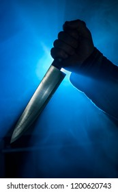 Close-up of hand clutching a kitchen knife with eerie blue  background