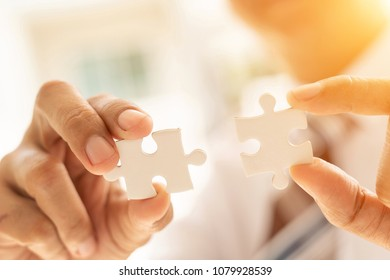 Closeup hand of connecting jigsaw puzzle with sunlight effect, Business solutions, success and strategy concept