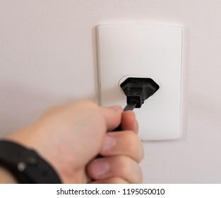 Close-up hand connecting plug socket on eletrical power socket three (3) pin - Brazilian standard - Brazil
