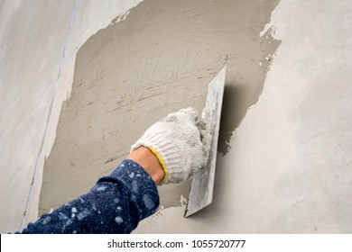 closeup hand construction plastering wet cement on the loft wall