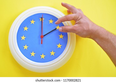 Close-up - a hand continues a clock with the colors of the EU flag for an hour - depicting the time change in the EU, as well as the vote on its abolition
