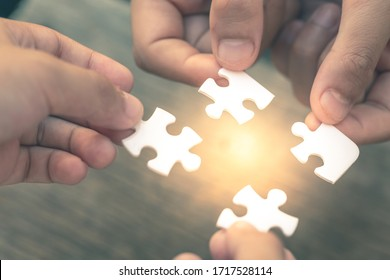 Closeup hand of diverse people connecting jigsaw puzzle which is a team work of the business detail blur