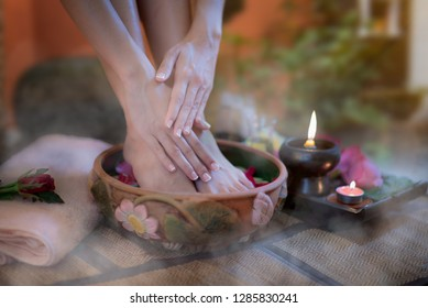 Closeup of hand of a female and feet at spa salon on pedicure procedure. Female legs in water decoration the flowers, relax and feel comfortable zone spa therapy and treatment