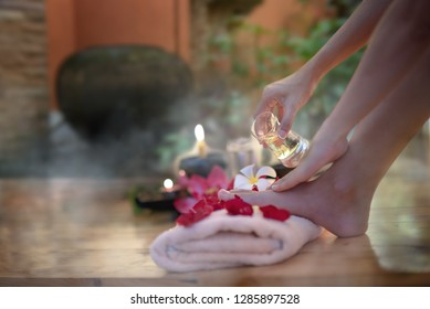 Closeup of hand female holding oil glass salon on feet pedicure procedure. Female legs on decoration the flowers towels, relax and feel comfortable zone spa therapy and treatment