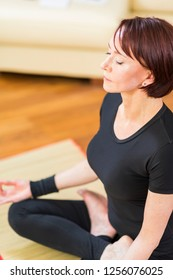 Closeup of Hand Fingers of Caucasian Brunette Woman Practicing Yoga Indoors. Doing Sukhasana Exercises In Therapy Pose. In Front of Sunny Window in Background. Vertical Image