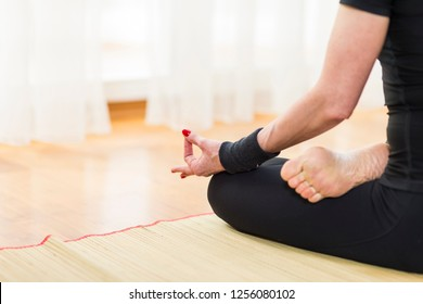 Closeup of Hand Fingers of Caucasian Brunette Woman Practicing Yoga Indoors. Doing Sukhasana Exercises In Lotus Therapy Pose. In Front of Sunny Window in Background.Horizontal Image