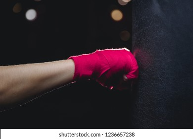 Close-up of hand in fist pink protective insulating bandage hits punching bag on black background. Concept Boxing