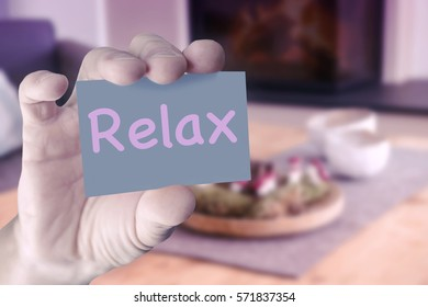 closeup of hand in front of living room holding a card with the word Relax