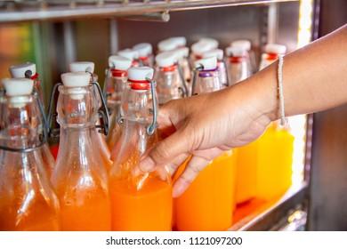 Closeup hand grap orange juice bottle