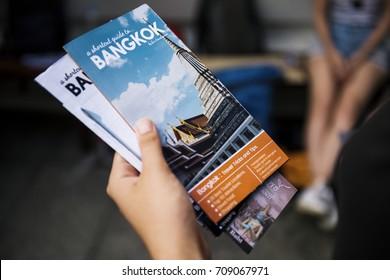 Closeup of hand holding Bangkok travel guide brochure