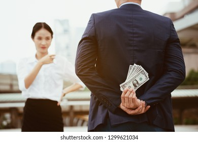 Closeup hand holding banknotes In back of the businessman, Women standing to investigate suspicions of financial irregularities in investment. That looks fraudulent Not in accordance with law of bank