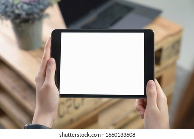 Close-up of hand holding black tablet on sofa in living room.
