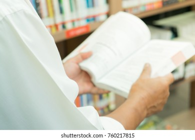 Close-up hand holding book with over shoulder angle and shallow depth of field.Select focus on the book.