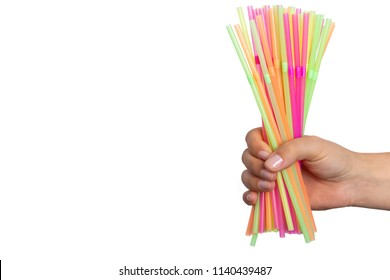 Closeup of hand holding colorful drink straws as party harmful single use disposable plastic object concept isolated on white background