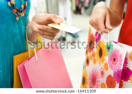 Close-up of womanâ??s hand holding credit card and bags with another female near by during shopping in the mall