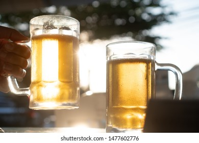 Closeup hand holding fresh lager beer mugs with sun rays in hot summer day