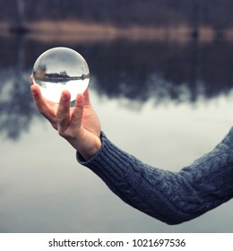 closeup of hand holding a glass ball in front of lake
