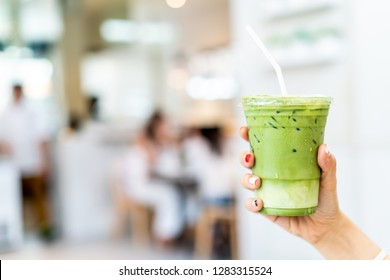 close-up hand holding iced matcha latte green tea cup