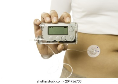 closeup of a hand holding an insulin pump isolated on a white background