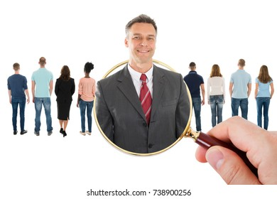 Close-up Of Hand Holding Magnifying Glass Searching Candidate For Recruitment