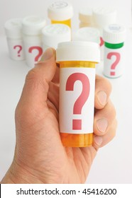 closeup of a hand holding a medicine bottle marked with a large question mark. In background is a group of pill bottles all labeled with large question marks. Background is moderately out of focus.