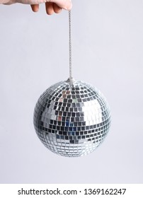 closeup. hand holding a mirror ball.isolated on gray background