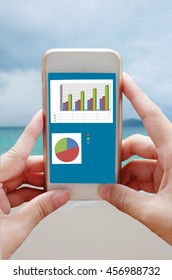 Closeup hand holding mobile phone show analyzing graph with sea background
