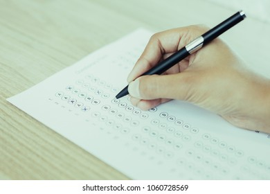 Closeup of hand holding pen and filling out questionary form on table