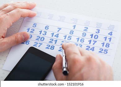 Close-up Of Hand Holding Pen Over Calendar With Mobile Phone