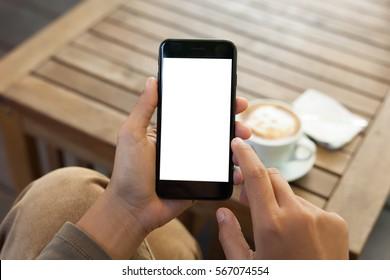 Nahaufnahme von Hand, die ein Mobiltelefon mit Leerbildschirm und Fingerberührung im Kaffeehaus hält
