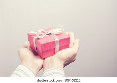 Closeup, Hand holding red gift box, female giving gift, New year holidays and greeting season concept, retro filter.