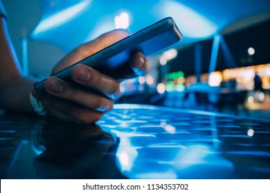 Close-up hand holding smart phone on night bar background with blue lighting. Young woman sitting at table in cafe and texting.