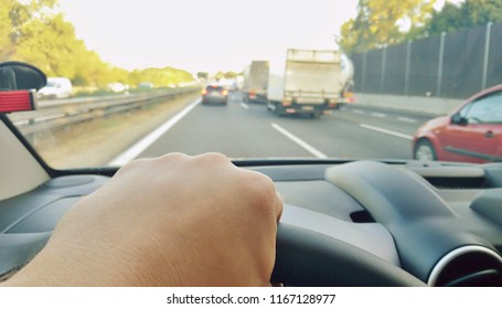 Closeup of hand holding steering wheel during driving a car on highway. POV shot, point of view first person perspective.