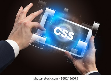 Close-up of a hand holding tablet with CSS abbreviation, modern technology concept