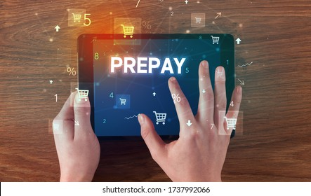 Close-up of a hand holding tablet with PREPAY inscription, online shopping concept