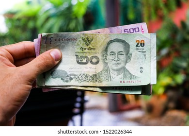 Closeup of a hand holding thai baht banknotes in a green cafe