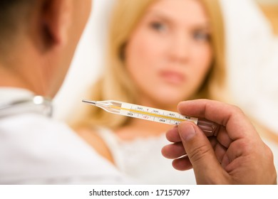 Close-up of doctor�s hand holding thermometer with sick woman on background