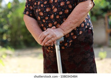 Closeup hand holding Walking stick of senior woman