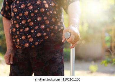 Closeup hand holding Walking stick of senior woman