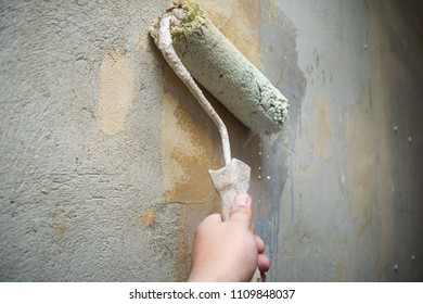 Close-up hand holds rolling paint brush, painting interior stucco wall with white color.Preparation of walls for painting or wallpapering, priming with a roller