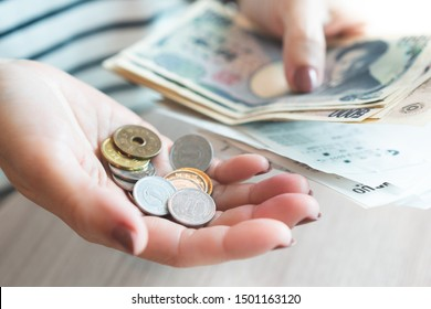 Closeup: Hand of a house wife holding wads of Japanese banknote with sale slips from the convenience store and small coins in the other hand. Japan, Cash based society, Cost of living, Expenses, Woman