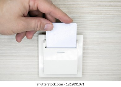 Closeup hand insert key card to opening light electronic in hotel room. Hotel room key card in electronic lock on the wall