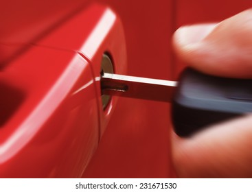 Closeup of hand inserting key into car lock with zoom blur