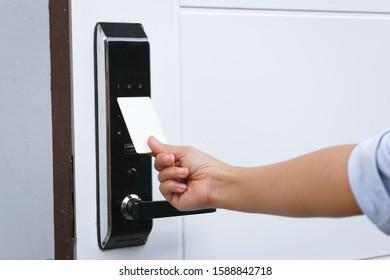 Close-up hand inserting keycard to lock and unlock door - Door access control keypad with keycard reader.