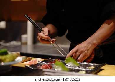 Close-up hand of Japanese chef making sushi, decorating cucumber on black background. The chef decorates cucumber sushi before serving.