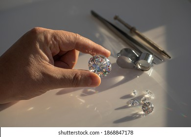 Close-up of the hand of jeweller gemologist with large size round cut diamond on desktop with magnifier and tweezers. Buyer diamond expert checking color of diamond in natural light.