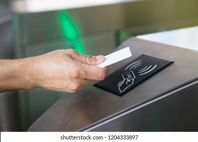 Close-up hand with keycard at pedestrian access control flap barriers.