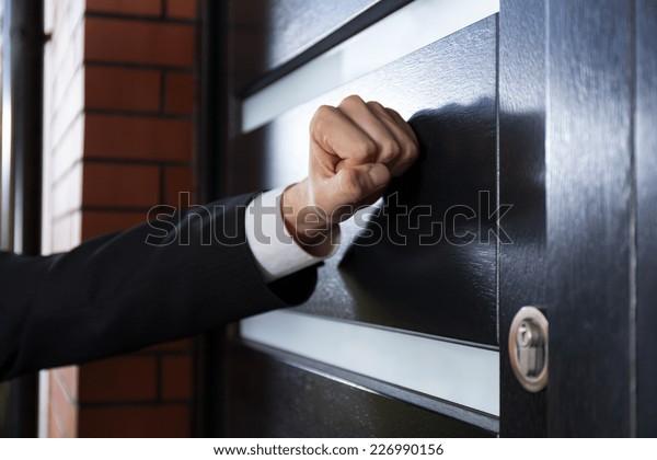 Gros plan sur une main frappant à la porte