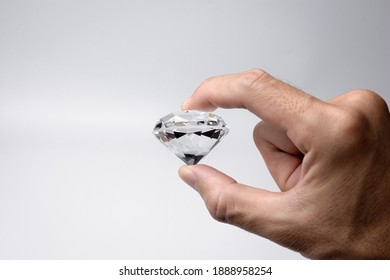Close-up of the hand with large size round cut diamond on white background.