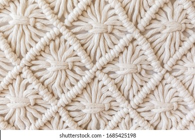 Close-up of hand made macrame texture pattern. ECO friendly modern knitting DIY natural decoration concept. Flat lay.